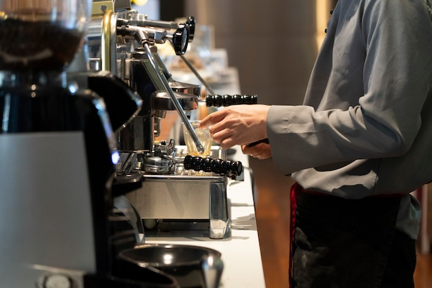 Vista del barista en el café haciendo una taza de café con la maquinaria de elaboración de café.