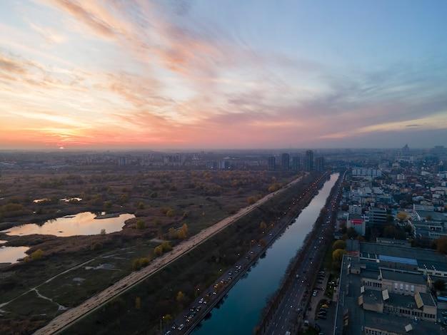 Vista de bucarest desde el dron, canal de agua, parque con vegetación y lagos, múltiples edificios residenciales y comerciales, puesta de sol, rumania
