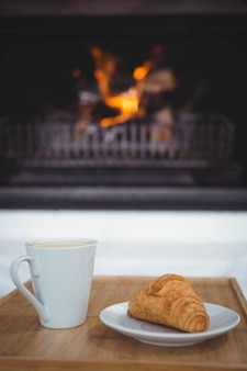 Vista de café y croissant en una mesa en la sala de estar