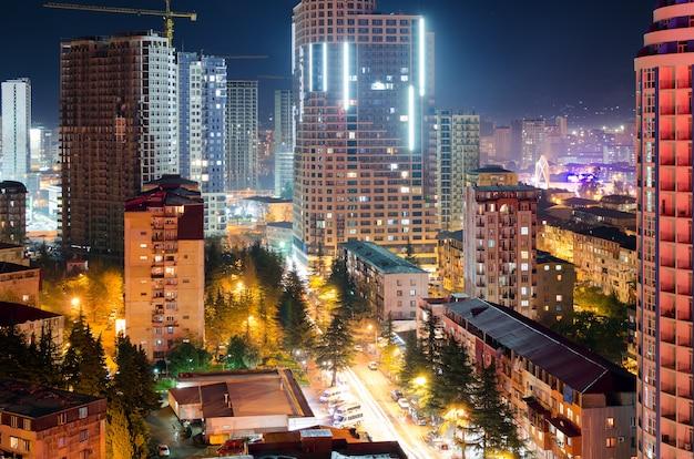 Vista de las calles de la ciudad nocturna de batumi con rascacielos, luz de las ventanas de los edificios de apartamentos, tráfico de automóviles en la carretera. vida urbana.