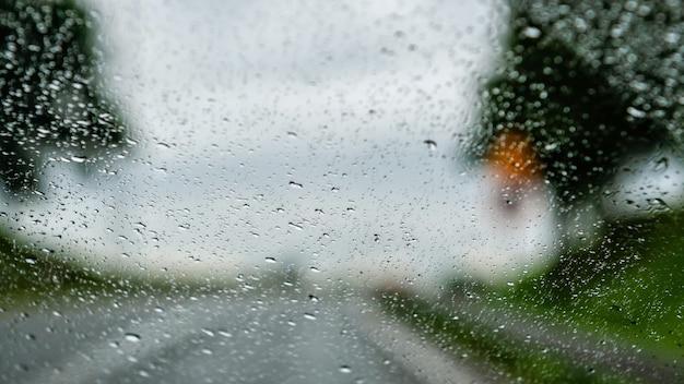 Vista del camino a través de la ventana cubierta de gotas de lluvia
