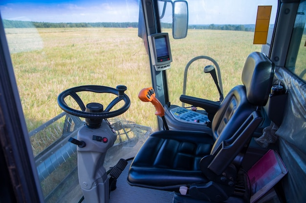 Vista del campo de maíz desde la cabina de una cosechadora en un día soleado. lugar de trabajo de un operador de cosechadora.