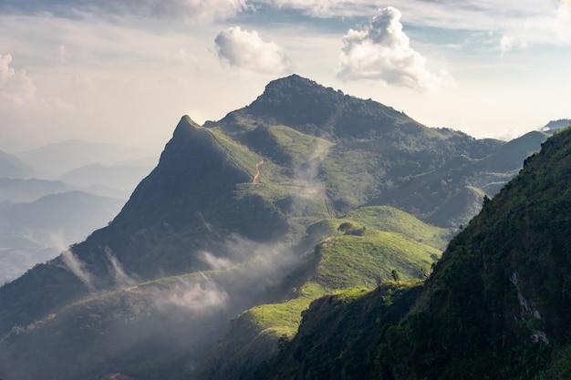 Vista de las capas de picos verdes, montañas y nubes de flujo de niebla, con derrota al pico. paisaje de la naturaleza