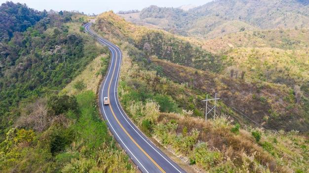 Vista de carretera con coche en la montaña desde arriba.