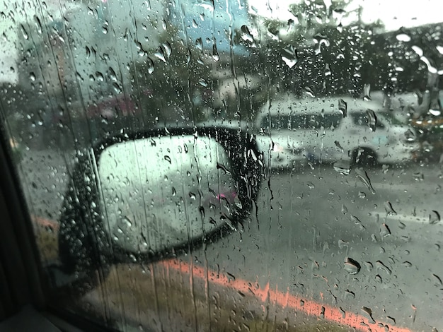Vista de la carretera a través de la conducción de automóviles en gotas de lluvia
