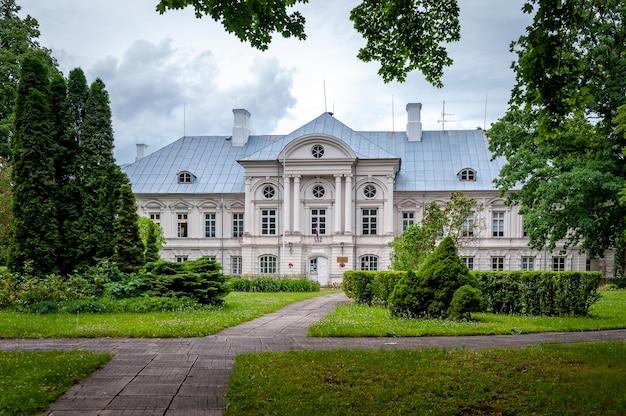 Vista del castillo blanco a través del parque. zalenieki manor, green manor, letonia.