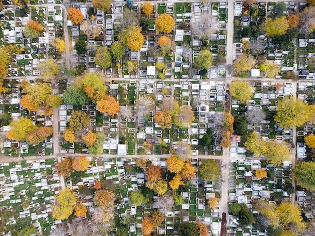 Vista de un cementerio con muchas tumbas y árboles amarillentos desde el zumbido, vista superior, bucarest, rumania