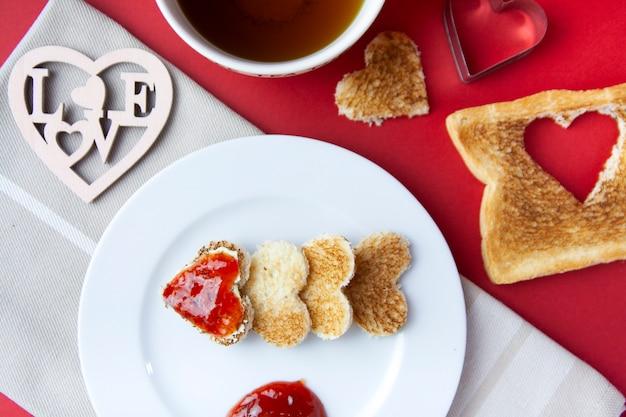 Vista cenital del desayuno romántico con tostadas y mermelada.