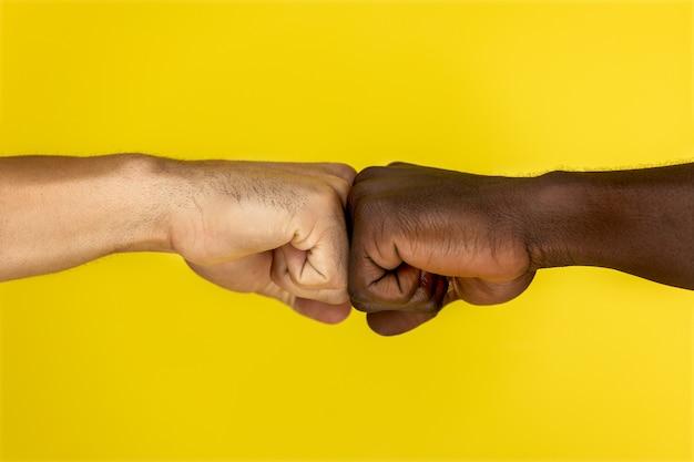 Vista central de europeos y afroamericanos mano a mano apretados en puños