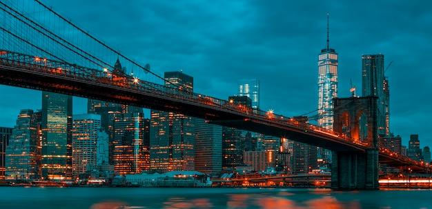 Vista del centro de manhattan de nueva york al anochecer con el puente de brooklyn.