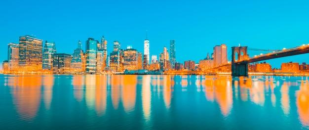 Vista del centro de manhattan de nueva york al anochecer con rascacielos iluminados sobre east river