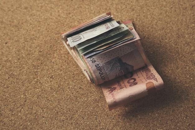 Vista de cerca de un alto ángulo de dinero en efectivo sobre un fondo marrón