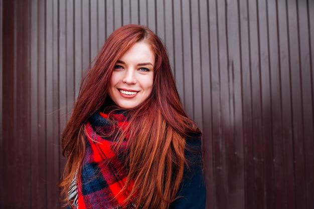 Vista de cerca de atractiva mujer caucásica feliz con cabello pelirrojo vistiendo ropa elegante mirando y sonriendo