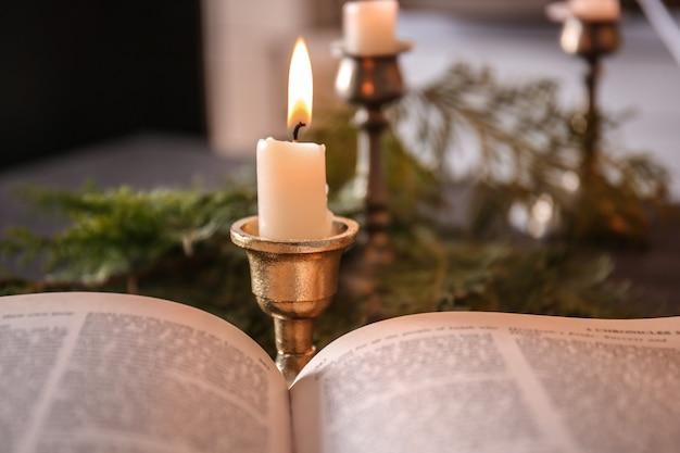 Vista de cerca de la biblia abierta y velas encendidas sobre fondo borroso