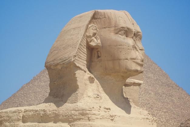 Vista de cerca de la cabeza de la esfinge con pirámide en giza, cerca de el cairo, egipto