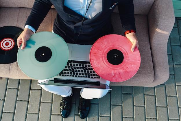 Vista de cerca chico en traje formal, discos de vinilo y laptop