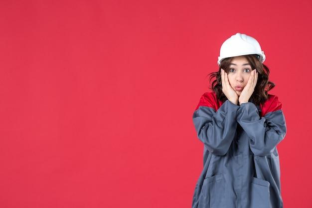 Vista de cerca del constructor femenino sorprendido en uniforme con casco en pared roja aislada