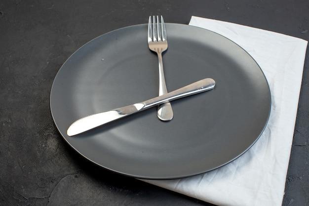 Vista de cerca de cubiertos de acero inoxidable en una placa negra sobre una toalla blanca sobre fondo de color oscuro