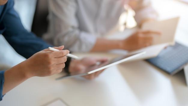 Vista de cerca de dos hombres de negocios que consultan sobre su proyecto con tableta digital y archivo de documentos