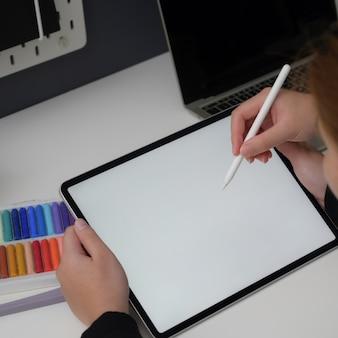 Vista de cerca de dos informes del diseñador sobre su proyecto con tableta simulada y suministros de diseño