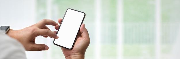 Vista de cerca del empresario con smartphone de pantalla en blanco en la sala de la oficina de pared de vidrio