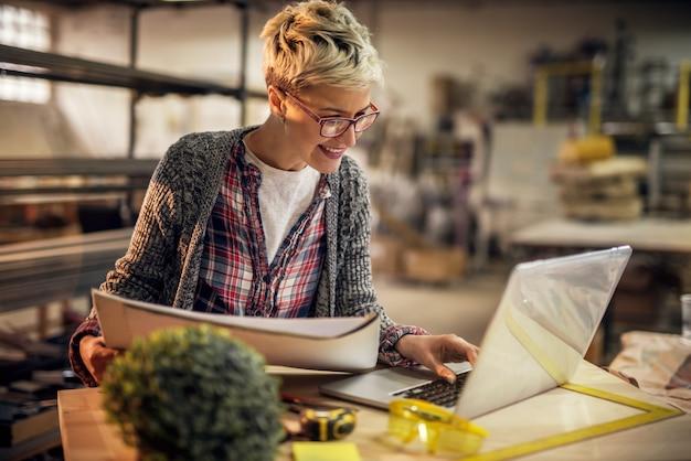 Vista de cerca de encantadora sonrisa motivada ingeniera de cabello corto con anteojos trabajando con planos y laptop en el taller