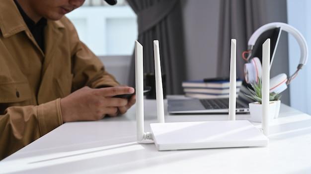 Vista de cerca de un enrutador inalámbrico con el empresario usando una computadora portátil y un teléfono inteligente en el fondo de la oficina en casa.