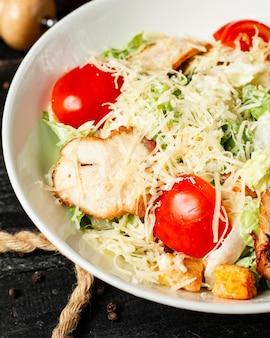 Vista de cerca de ensalada césar con tomate pollo y queso parmesano en un tazón
