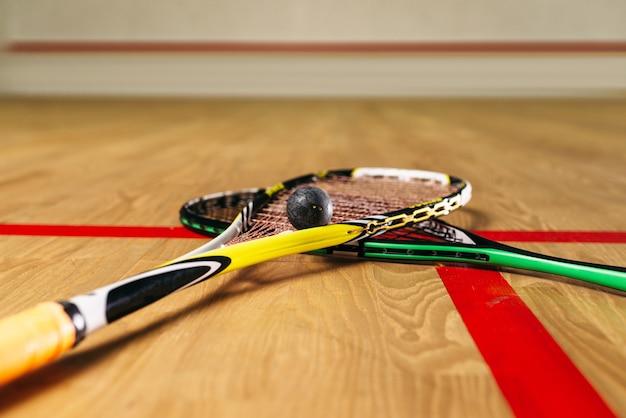 Vista de cerca del equipo de juego de squash. raquetas y pelota en el suelo en el club de entrenamiento de interior