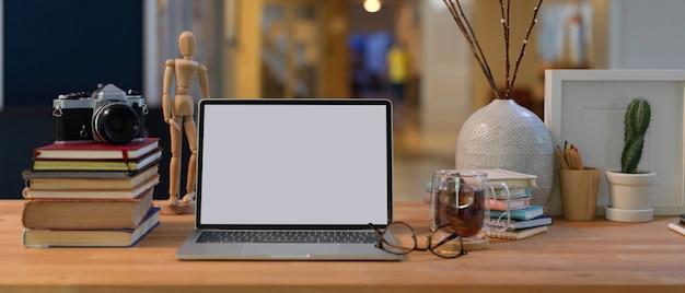 Vista de cerca del espacio de trabajo con maquetas de portátiles, libros, suministros y decoraciones en el escritorio de madera en la sala de oficina