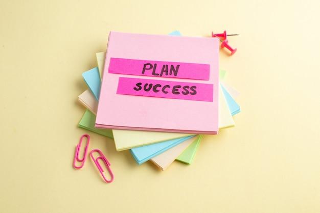 Vista de cerca del éxito del plan escribiendo en cubos de notas adhesivas apiladas y clips de papel chinchetas sobre fondo amarillo con espacio libre