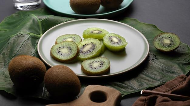 Vista de cerca de la fruta de kiwi fresca en rodajas en un plato y toda la fruta de kiwi en la mesa de la cocina