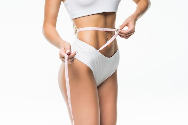 Vista de cerca de una hermosa mujer joven con una cinta métrica aislada en la pared blanca