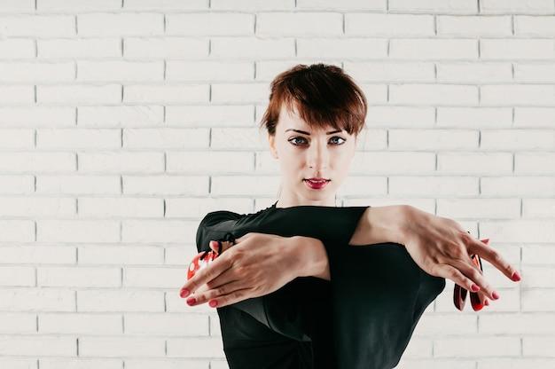 Vista de cerca de una hermosa mujer vestida de negro, bailando con castañuelas rojas