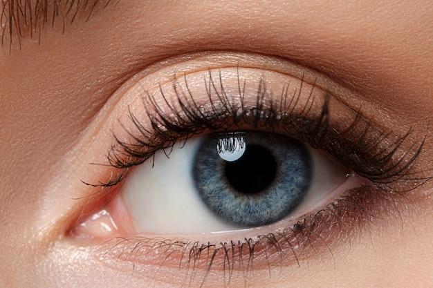 Vista de cerca del hermoso ojo femenino azul. buena visión, lentes de contacto, confianza o concepto de observación.