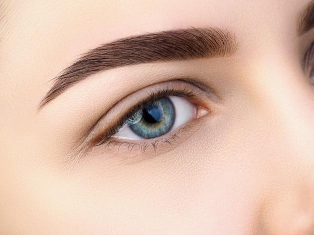 Vista de cerca del hermoso ojo femenino azul. ceja de moda perfecta. buena visión, lentes de contacto, barra de cejas o concepto de maquillaje de cejas de moda