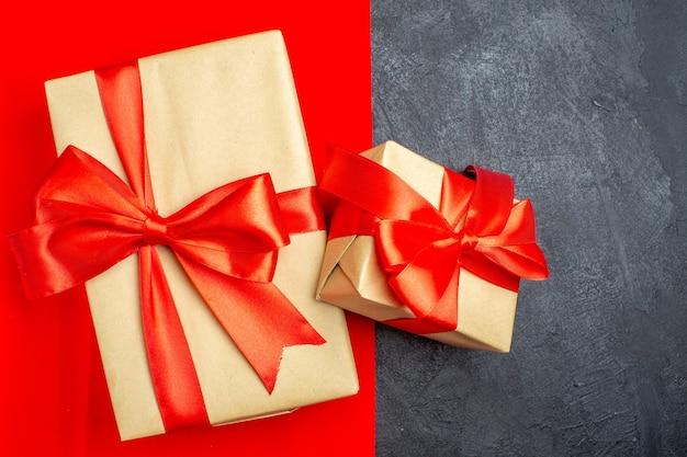 Vista de cerca de hermosos regalos con cinta en forma de arco sobre fondo rojo y negro