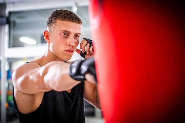 Vista de cerca hombre entrenando con saco de boxeo