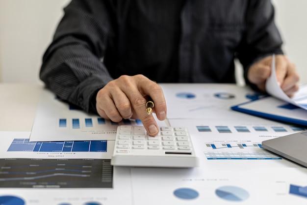 Vista de cerca un hombre de negocios que usa una calculadora para calcular números en los documentos financieros de una empresa, está analizando datos financieros históricos para planificar cómo hacer crecer la empresa. concepto financiero.