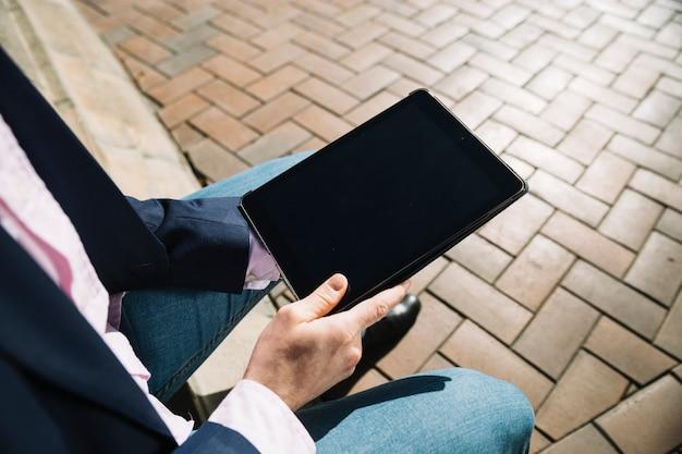 Vista de cerca de hombre de negocios usando tableta al aire libre