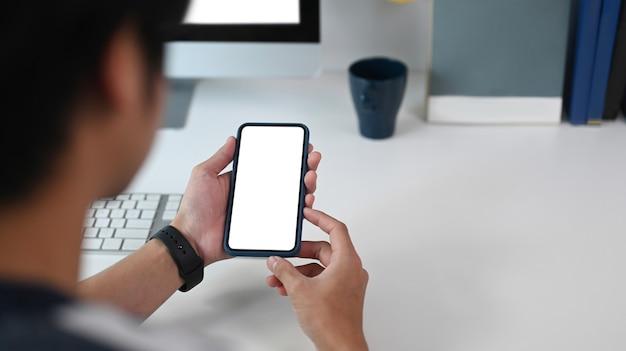 Vista de cerca del joven sosteniendo un teléfono inteligente con pantalla vacía en su escritorio de oficina.