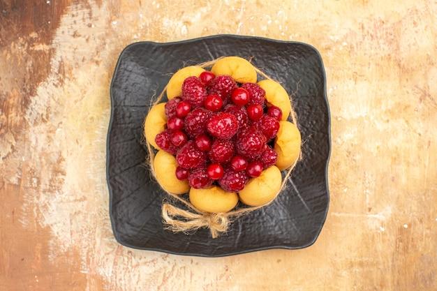 Vista de cerca del juego de mesa para la hora del té y café con frambuesas en tortas en la mesa de colores mezclados