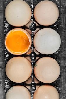 Vista de cerca laicos plana huevos crudos y pasados por agua en caja de plástico.