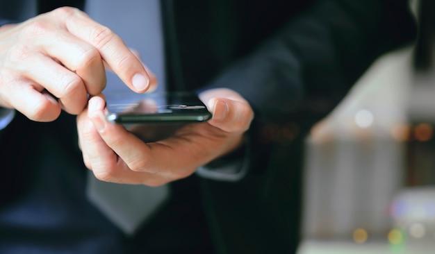 Vista de cerca de la mano del empresario con smartphone.