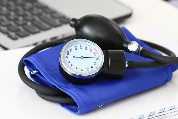 Vista de cerca del manómetro en la mesa de trabajo cerca de la computadora portátil. espacio de trabajo del hospital. concepto de salud, servicio médico, tratamiento, hipotonía o hipertensión.