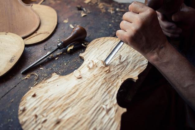Vista de cerca de las manos del carpintero moldeando y tallando madera en su antiguo taller