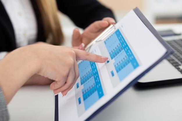 Vista de cerca de las manos de dos mujeres sentadas en la oficina y mirando gráficos y tablas discutiendo algunas preguntas