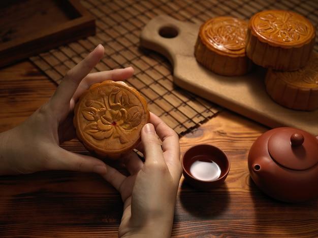 Vista de cerca de manos femeninas sosteniendo pastel de luna tradicional con tetera, taza y pasteles de luna en mesa de madera