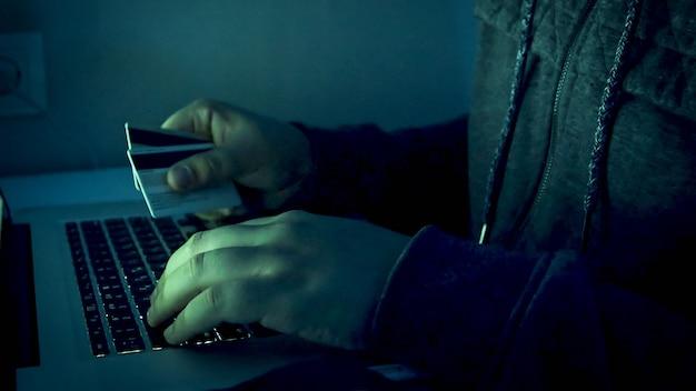 Vista de cerca de las manos del hacker masculino sosteniendo tarjetas de crédito y escribiendo en la computadora portátil por la noche