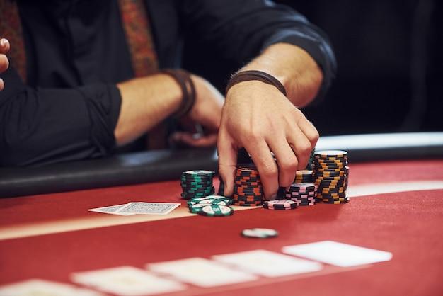 Vista de cerca de las manos del hombre. guy juega al póker por mesa en el casino